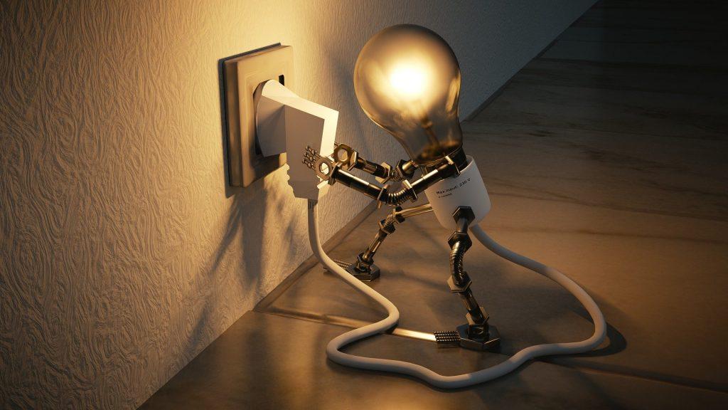 A light bulb mechanical figure plugs itself into an electrical socket.